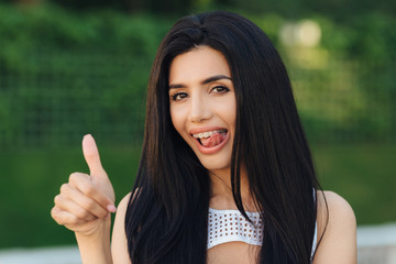 Beautiful young lady with happy expression, shows ok sign, keeps thumb raised, shows tongue and teeth with braces, approves something with positiveness, poses outdoor against green background © VK Studio