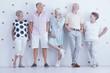 Fashionably dressed smiling senior people posing in bright studio