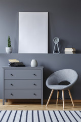 Grey armchair next to cabinet in apartment interior with mockup of empty poster. Real photo