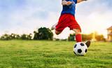 Obraz sportu akcji grupy dzieci grających w piłkę nożną do ćwiczeń w obszarze wiejskim społeczności pod zachodem słońca.