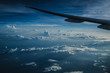 Wing of airplane above island while the sun is going down with lots of clouds in the sky. Traveling concept - 208778162