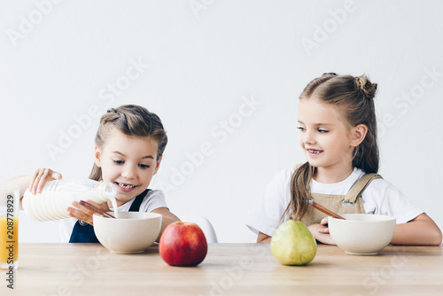 Leinwanddruck Bild adorable smiling schoolgirls pouring milk into bowls with cereals isolated on white