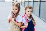 smiling little schoolgirls with pink backpacks on street looking at camera