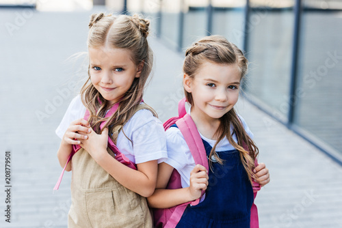 smiling little schoolgirls with pink backpacks on street looking at camera © LIGHTFIELD STUDIOS
