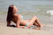 Young woman in bikini lying on the beach