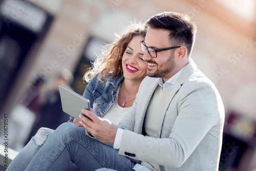 Couple with tablet on the street