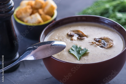 Mushroom cream soup in a brown plate on the table. Healthy vegetarian traditional dish - 208783348