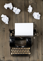 Vintage typewriter top down flatlay shot from above with empty, blank sheet of paper and crumbled paper balls on wood table