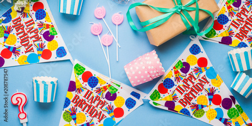 Foto Murales Happy Birthday party items flat lay. Candles, gift box, decoration banner, paper glasses, chocolate cake