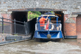 blue and cream canal boat being driven through small gap in tunnel under bridge in a tight fit - 208789520