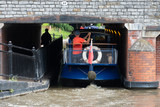 blue and cream canal boat being driven through small gap in tunnel under bridge in a tight fit - 208789543