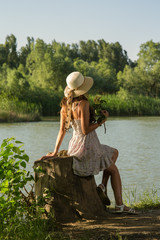 woman in a dress and hat sits on the river bank on a stump