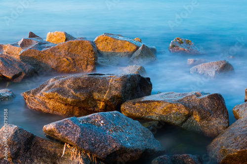 Sea rocks in haze at sunset