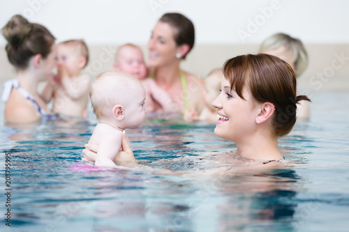 Leinwanddruck Bild Group of mums with their baby children at infant swimming class