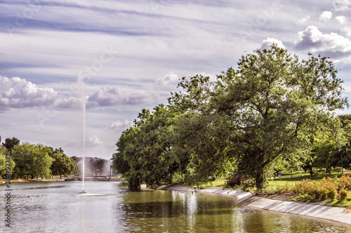 Foto Murales Parque Enrique Tierno Galván. paisaje con arboles, laguna y chorro vertical sobre fondo con nubes en el parque de Enrique Tierno Galván en Madrid. España.
