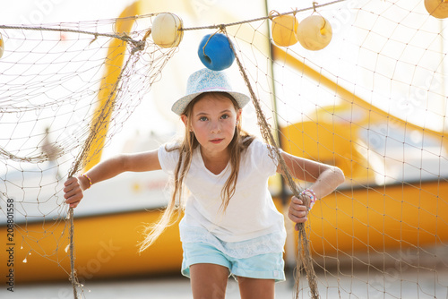 Foto Murales Young girl hiding behind fishing net on the beach