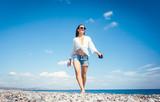 Frau macht einen Spaziergang am Strand - 208802568