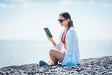 Frau liest einen Roman als e-book am Strand