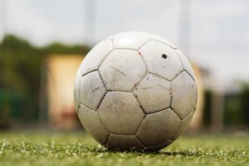 Football or soccer ball on football field