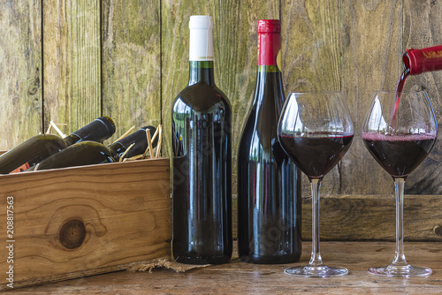 Bottles of red wine and wineglasses on rustic background
