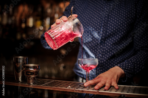 Leinwanddruck Bild Barman pouring fresh and sweet pink summer cocktail into the glass