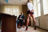 Woman dominant with whip in office
