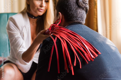 Woman put whip on man shoulder - 208820555