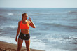 Young fitness woman drinking water by the sea