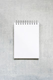 Blank sheet of notepad on the textured grey table - 208822737