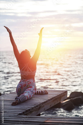 woman playing yoga pose on beach pier against sun rising sky