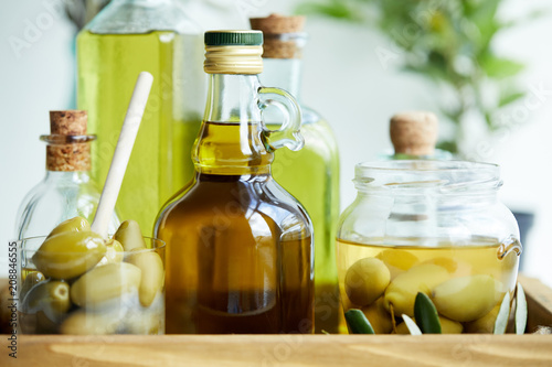 Leinwanddruck Bild glass with spoon and green olives, jar, various bottles of aromatic olive oil with and branches on wooden tray