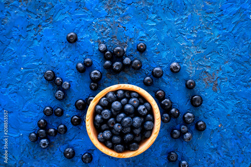 Fresh recently picked blueberries in bowl on blue background top view copy space - 208853557