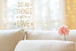 Do All Things with Love message with a flower in a bright interior room sofa