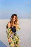 Young woman wearing green beach robe standing on white sand. Concept of photo session in desert and summer. - 208857390