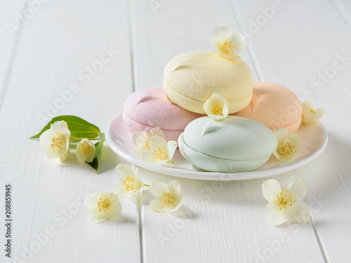 Colorful macaroons with Jasmine flowers on a white wooden table.