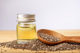 Close up a Chia essential oil and seeds in wooden spoon , a superfood and rich of nutrient an antioxidant