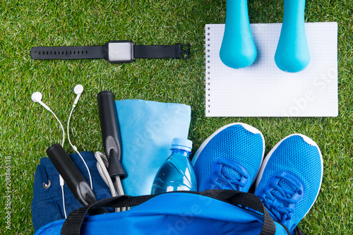 Fotobehang Hardlopen blue set of things for cardio workout, on a green lawn with a smart clock