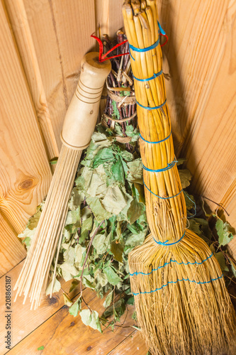 Three different brooms stand on a bench in the sauna - 208865187