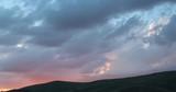 clouds ocer the hills at dusk - 208866110