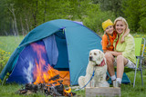 Family tourist near his camp tent at campfire with dog. - 208866502