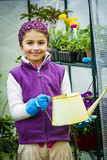 Beaitful child playing in greenhouse and care for plants. Cute girl engaged in gardening in the backyard. Spring organic growth concept. - 208866781
