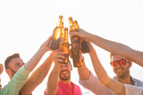 Cheers! Group of happy young people are toasting with bottles of beer in the beach. Celebration concept - 208867733