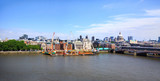 Panorama of The City of London overlooking The River Thames with various iconic buildings against a blue cloudy sky
