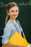 Beatiful smiling pupil in classroom at the elementary school, back to school. - 208868789