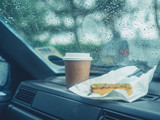 Paper cup and cake on dashboard