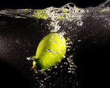 Green avocado in water on a black background