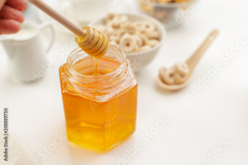 Sticker Pouring aromatic honey into jar, closeup