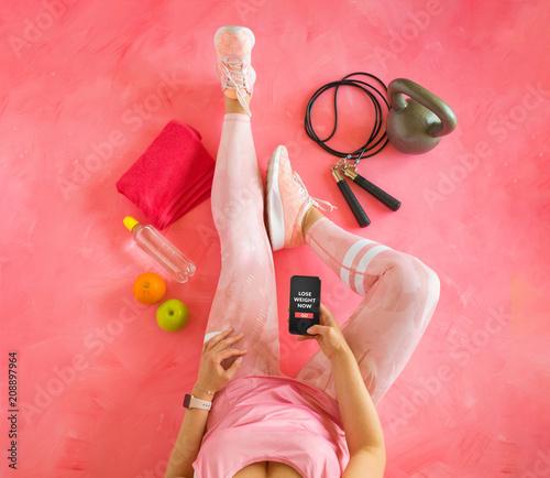 Kobieta trzyma telefon komórkowy z app fitness gotowy do treningu utraty wagi.