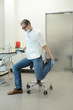 male dentist stretching his legs  in the office during break - 208898562