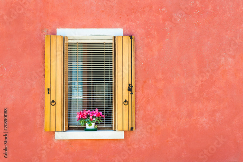Plexiglas Koraal Window with wooden shutters on the red wall. Colorful houses in Burano island, Venice, Italy